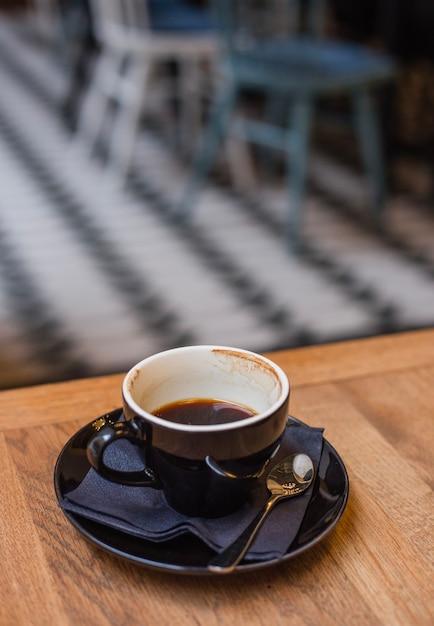 朝の木製テーブルに半分フルエスプレッソコーヒーの黒いカップ Premium写真