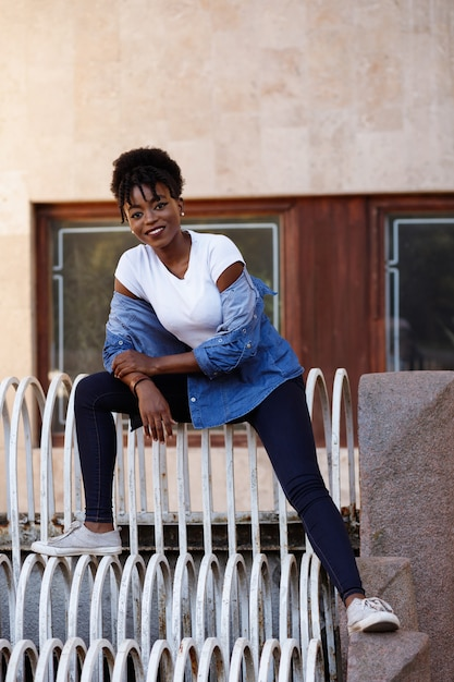 街の階段に黒人の女の子が座っています。平等 Premium写真
