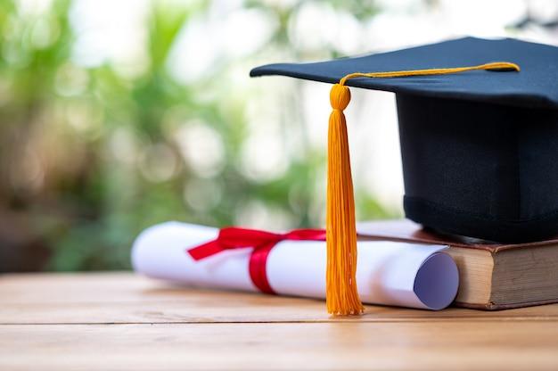 古い本に置かれた黒い卒業帽と証明書 Premium写真