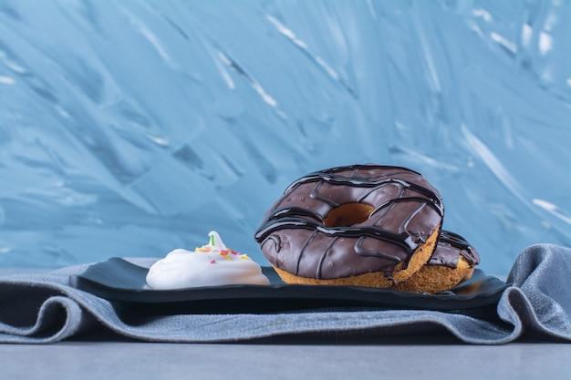 テーブルクロスに甘いチョコレートドーナツの黒いプレート。 無料写真
