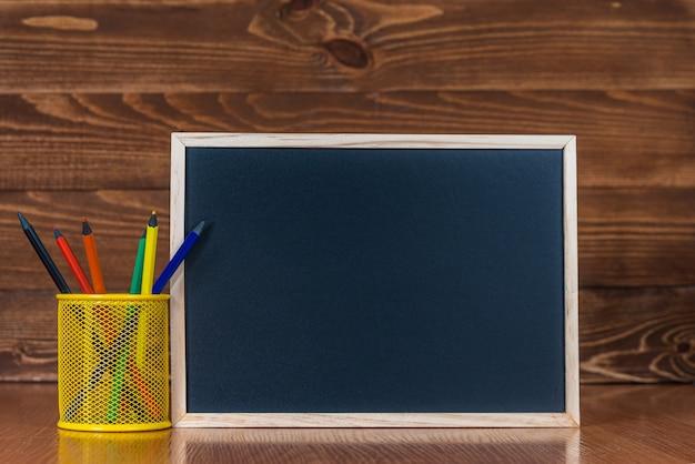 Доска с пространством для текста, набор цветных карандашей со стаканом на деревянном фоне Premium Фотографии