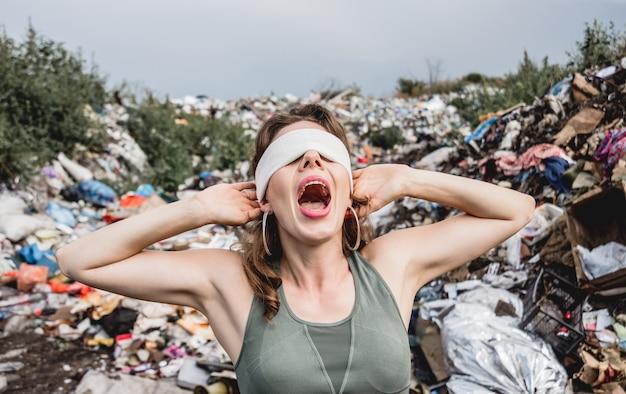 Женщина-волонтер с завязанными глазами кричит от бессилия на свалке пластикового мусора. день земли и экология. Premium Фотографии