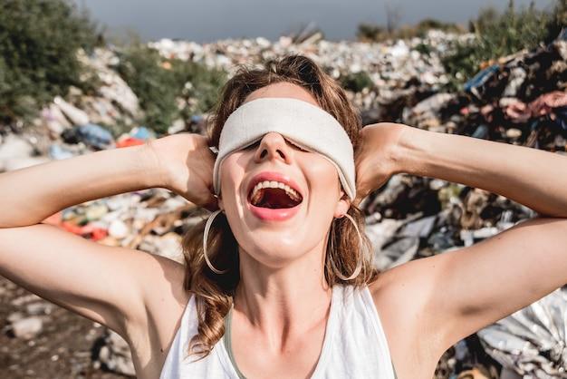Женщина-волонтер с завязанными глазами кричит от бессилия на свалке пластика Premium Фотографии