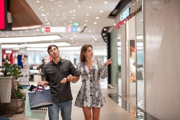 グレーのショートドレスと靴のブロンド、グレーのシャツを着た男と店から色のついたバッグを持ったブルージーンズ、手をつないでポーズ。男は目を転がします。女の子は店の窓を指しています。 Premium写真