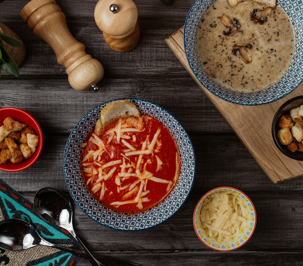 Синяя миска томатного супа с мелко нарезанным сыром пармезан сверху и грибным супом вокруг Бесплатные Фотографии