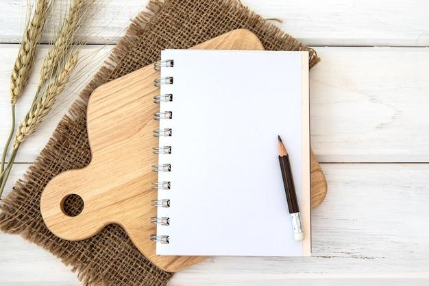 白いテーブル上のカッティングボードとテーブルクロスを切り刻むノートブックのノート紙 Premium写真