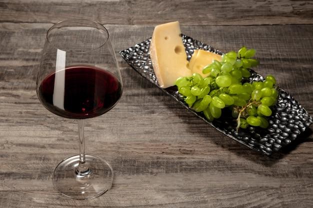 木製のテーブルの上にフルーツと赤ワインのボトルとグラス 無料写真