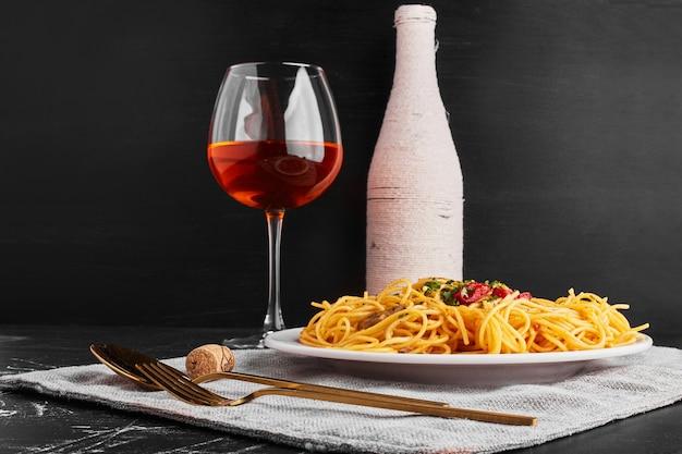 スパゲッティとロゼワインのボトルとグラス。 無料写真