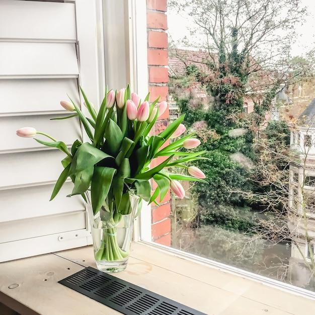 開いているシャッター付きの窓にガラスの花瓶にピンクのチューリップの花束 Premium写真