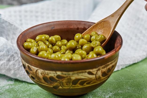 Миска вареного зеленого горошка деревянной ложкой на зеленом столе. Бесплатные Фотографии