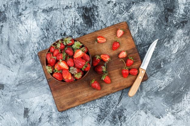 딸기와 어두운 파란색 대리석 배경에 나무 커팅 보드에 칼의 그릇. 평평한 평신도. 무료 사진