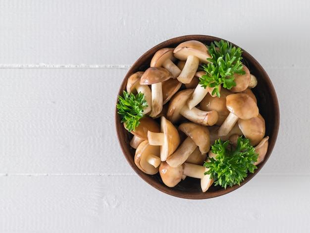 Миска лесных грибов и листьев петрушки на белом деревянном столе. вид сверху. натуральная вегетарианская кухня. Premium Фотографии