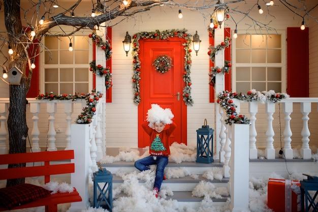 Мальчик в рождественском свитере сидит на ступеньках дома Premium Фотографии