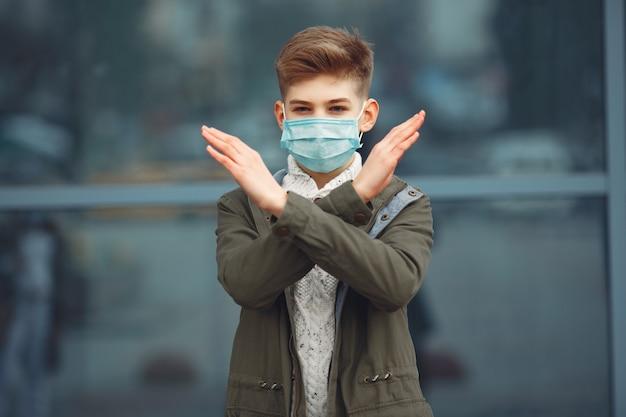 Мальчик в одноразовой маске скрещивает руки Бесплатные Фотографии
