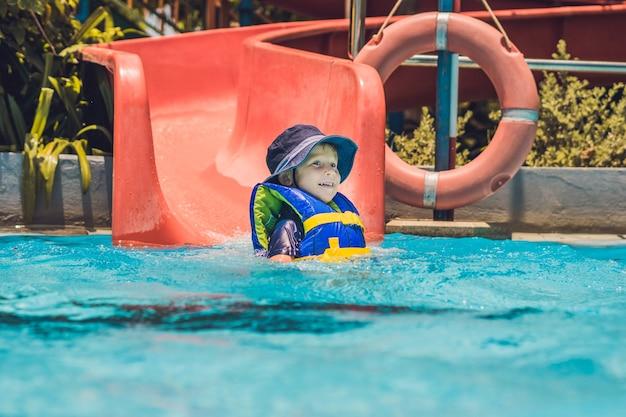 Мальчик в спасательном жилете соскальзывает с горки в аквапарке. Premium Фотографии