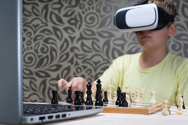 Мальчик в гарнитуру виртуальной реальности играет в шахматы с ноутбуком. научиться играть в шахматы с использованием информационных технологий Premium Фотографии