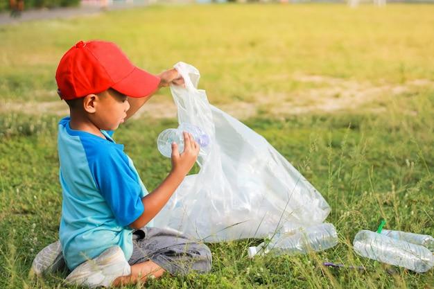 Мальчик - волонтер для уборки пола. он собирал много пластиковых бутылок и соломы на земле. Premium Фотографии