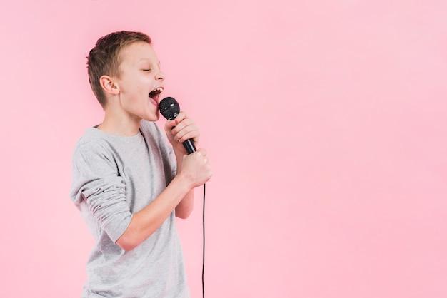 Мальчик поет песню в микрофон на розовом фоне Premium Фотографии