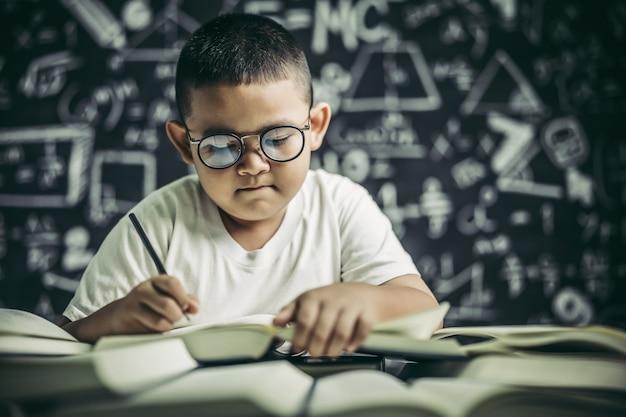 教室で書いている眼鏡の男の少年 無料写真
