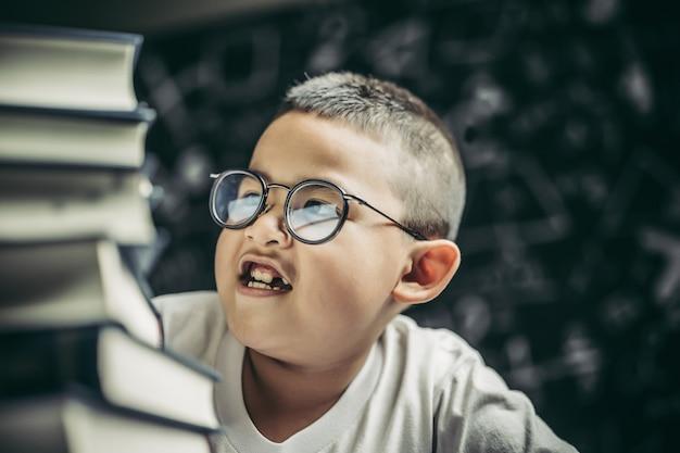 本を数える教室に座っている眼鏡の少年 無料写真