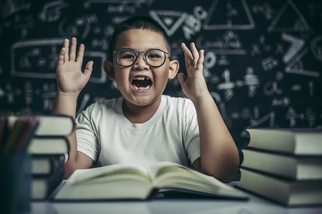 教室の読書に座っている眼鏡の少年 無料写真