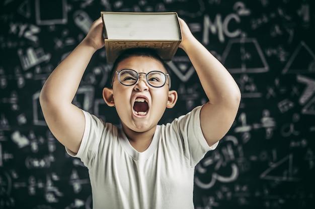 眼鏡をかけた男の子が教室で勉強し、頭に本を置きました。 無料写真