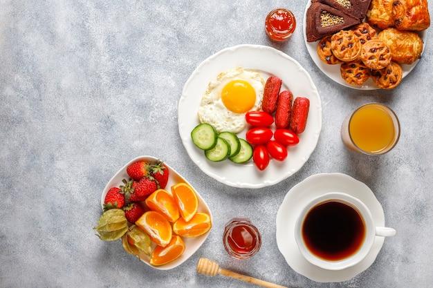 Блюдо для завтрака, содержащее коктейльные сосиски, яичницу, помидоры черри, сладости, фрукты и стакан персикового сока. Бесплатные Фотографии