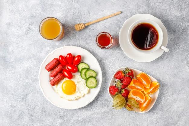 칵테일 소시지, 계란 후라이, 체리 토마토, 과자, 과일, 복숭아 주스 한 잔이 포함 된 조식 접시입니다. 무료 사진