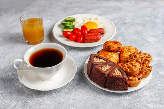 칵테일 소시지, 계란 후라이, 체리 토마토, 과자, 과일, 복숭아 주스 한 잔이 포함 된 조식 플레이트입니다. 무료 사진