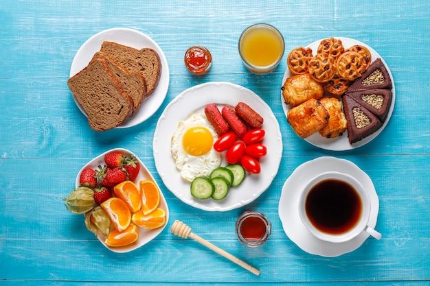 カクテルソーセージ、目玉焼き、チェリートマト、スイーツ、フルーツ、ピーチジュースのグラスが入った朝食プレート。 無料写真