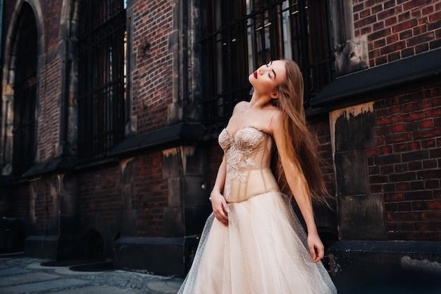 ヴロツワフの旧市街で長い髪のウェディングドレスを着た花嫁。ポーランドの古代都市の中心部での結婚式の写真撮影。ポーランド、ヴロツワフ。 Premium写真