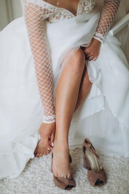 Невеста надеть свадебные туфли. красивый женский крупный план ног. Premium Фотографии