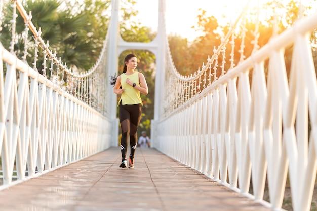 木製の橋の上を走っている明るい美しい女性 Premium写真