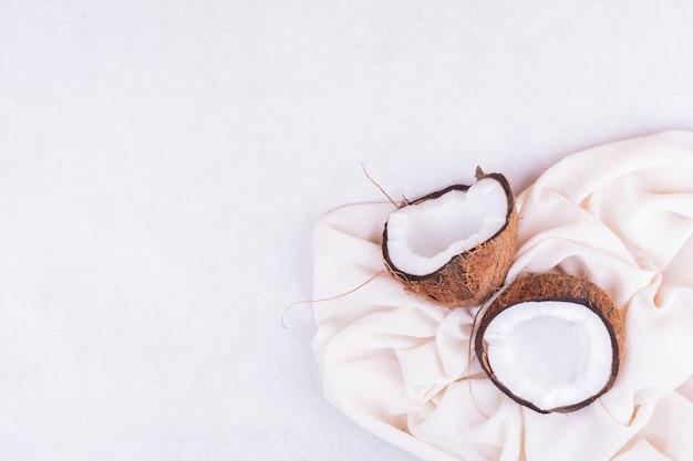 白いタオルで2つに切った茶色のココナッツ 無料写真