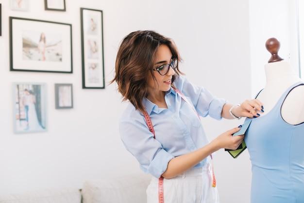Брюнетка создает синее платье в мастерской студии. в руках у нее шитье, смотрит на свою работу. на заднем плане много картинок. Бесплатные Фотографии