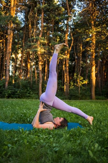 Брюнетка девушка выполняет перевернутую позу в природе на закате Premium Фотографии