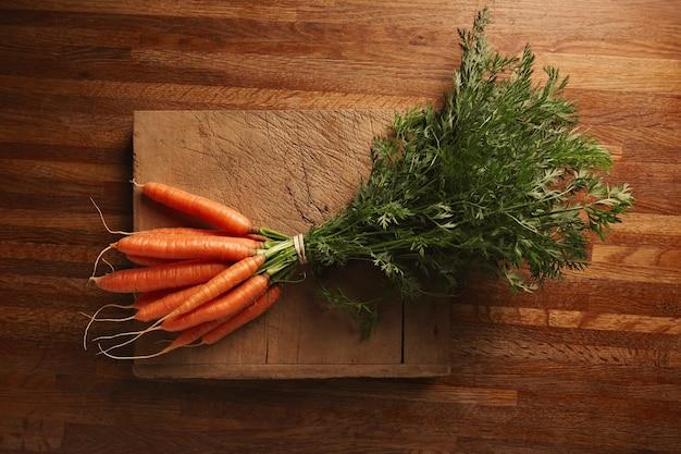 Пучок свежей моркови на обветренной старой разделочной доске с глубокими надрезами на красивом деревянном коричневом столе, вид сверху Бесплатные Фотографии