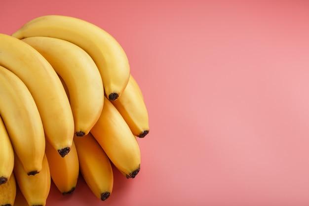 ピンクの背景に熟した黄色のバナナの束。上からの眺め。ミニマルなコンセプト。フリースペース Premium写真