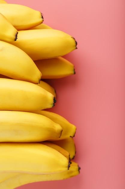 ピンクの背景に熟した黄色のバナナの束。 Premium写真