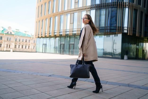 日中は、バッグを手に持ったコートとスーツを着たビジネスウーマンがビジネスセンターの近くを歩いています。 無料写真
