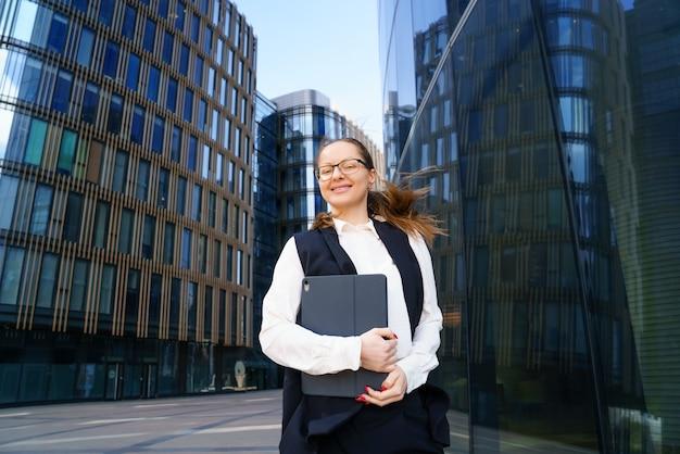 Деловая женщина стоит с ноутбуком в костюме и очках возле офисного здания днем. Бесплатные Фотографии