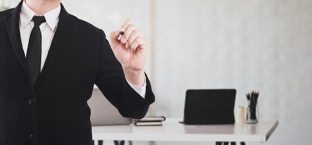 ビジネスマンが会議室に立っている間、ボード上で書くためのペンを指している Premium写真