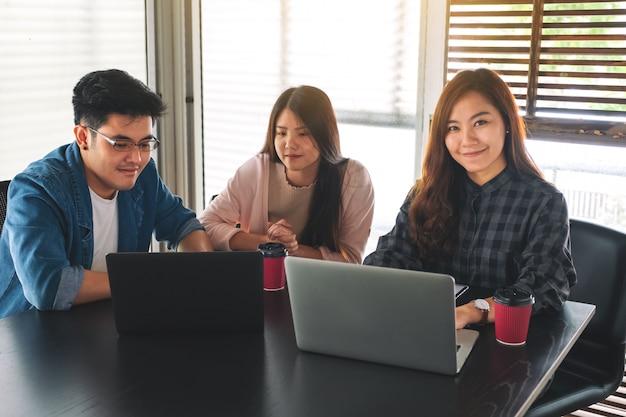 Коммерсантка работая и обсуждая о бизнес-данных с ее коллегами в офисе Premium Фотографии