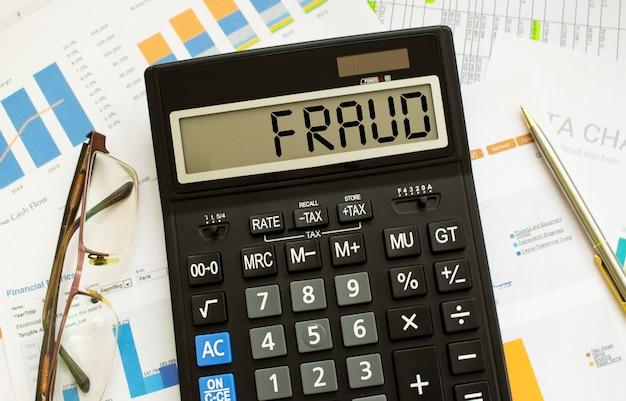 Калькулятор с надписью мошенничество лежит на финансовых документах в офисе. бизнес-концепция. Premium Фотографии