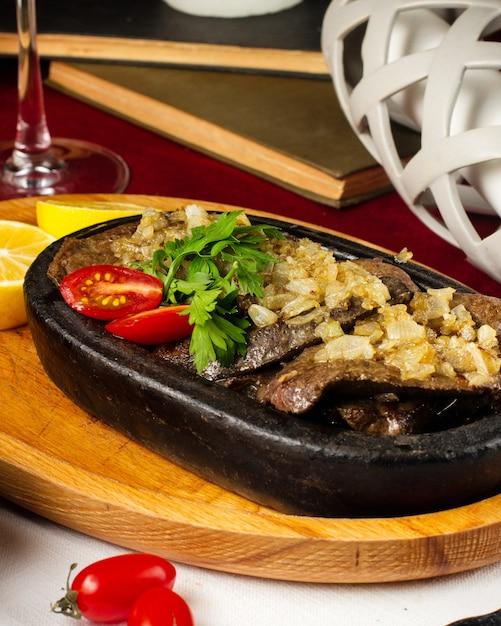 Чугунная сковорода с жареным мясом с обжаренным луком Бесплатные Фотографии