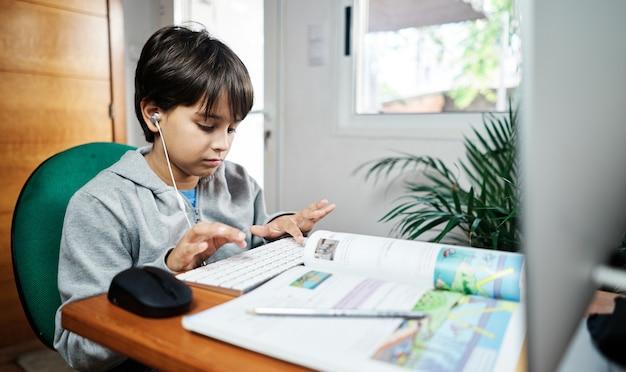 Белый мальчик учит дома по видеоконференцсвязи. ребенок заперт дома из-за covid-19. новый нормальный. школа в доме Premium Фотографии