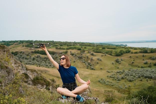 空と緑の岩が多い丘の上に座って、彼女の手でドローンを持つ白人女性 無料写真