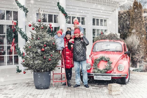 Веселая семья из четырех человек стоит рядом с красной машиной и весело проводит время Бесплатные Фотографии