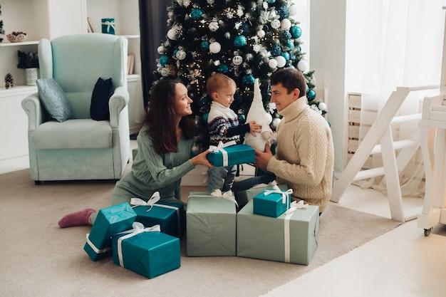 Веселая семья с маленьким ребенком вместе веселятся у елки Бесплатные Фотографии