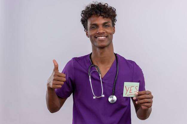 親指で「はい」という単語の紙のカードを示す聴診器で紫の制服を着た巻き毛の陽気な若いハンサムな浅黒い男性医師 無料写真